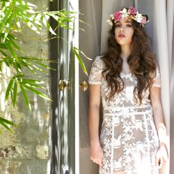 A young lady with long wave brunette hairstyle and wedding makeup looking directly at camera with wedding dress on and band of flowers in her hair.