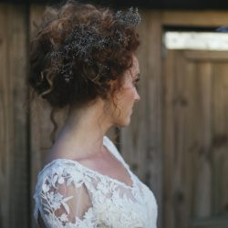 Beautiful upstyled curly hair on bride with ornamental flower piece looking away from camera