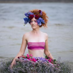 A woman wades in a lake with artistic curly red hairstyle with bright flowers and makeup while wearing a dress of flowers.