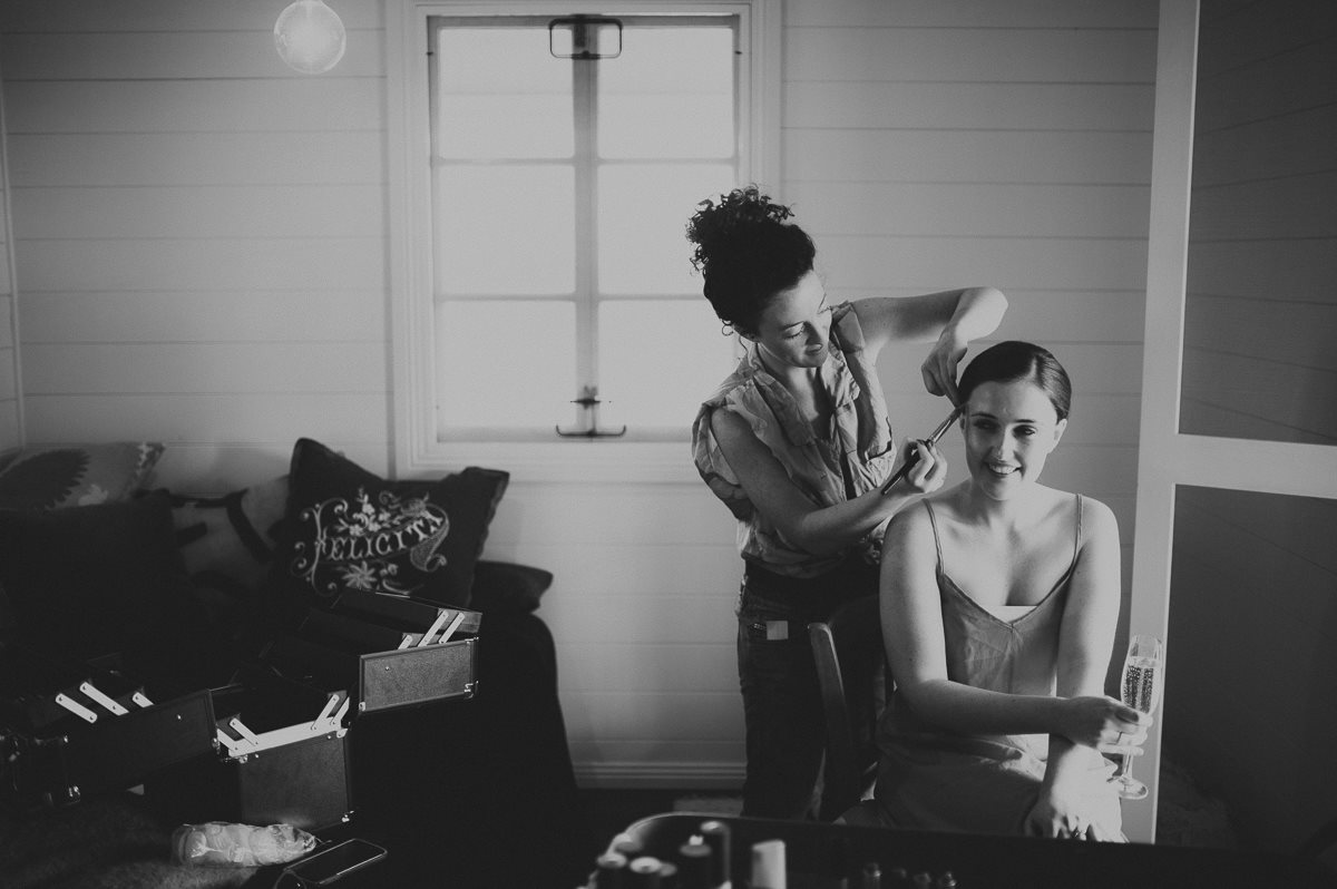 Black and white image of Emily K at her home salon styling womans hair for an event.